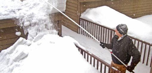 man using snow rake
