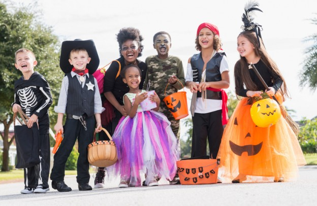 A multi-ethnic group of seven children wearing halloween costumes. They are mixed ages, from 3 to 10 years old, ready to go trick or treating.