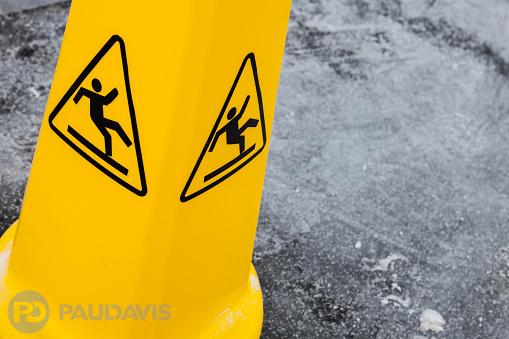Caution wet floor, yellow warning sign on asphalt